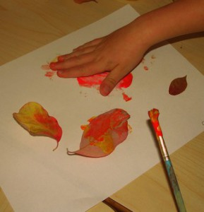 hands painting with leaves