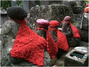 sculptures with knitted hats and bibs or scarves