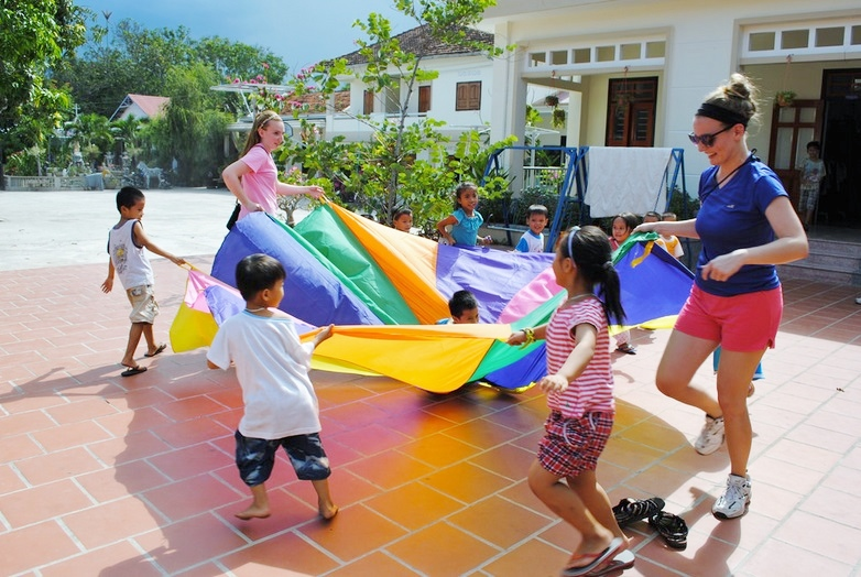 Students and children playing with a large parachute