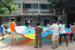 Adults and children playing outside with a parachute
