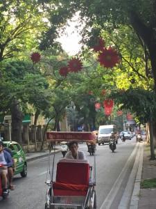 street scene in Hanoi - rickshaw & colorfuk flowers