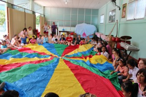 Children & adults with a multi-colored parachute
