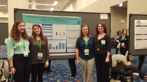 Ann Marie Potter and 3 recent graduates with poster presentation