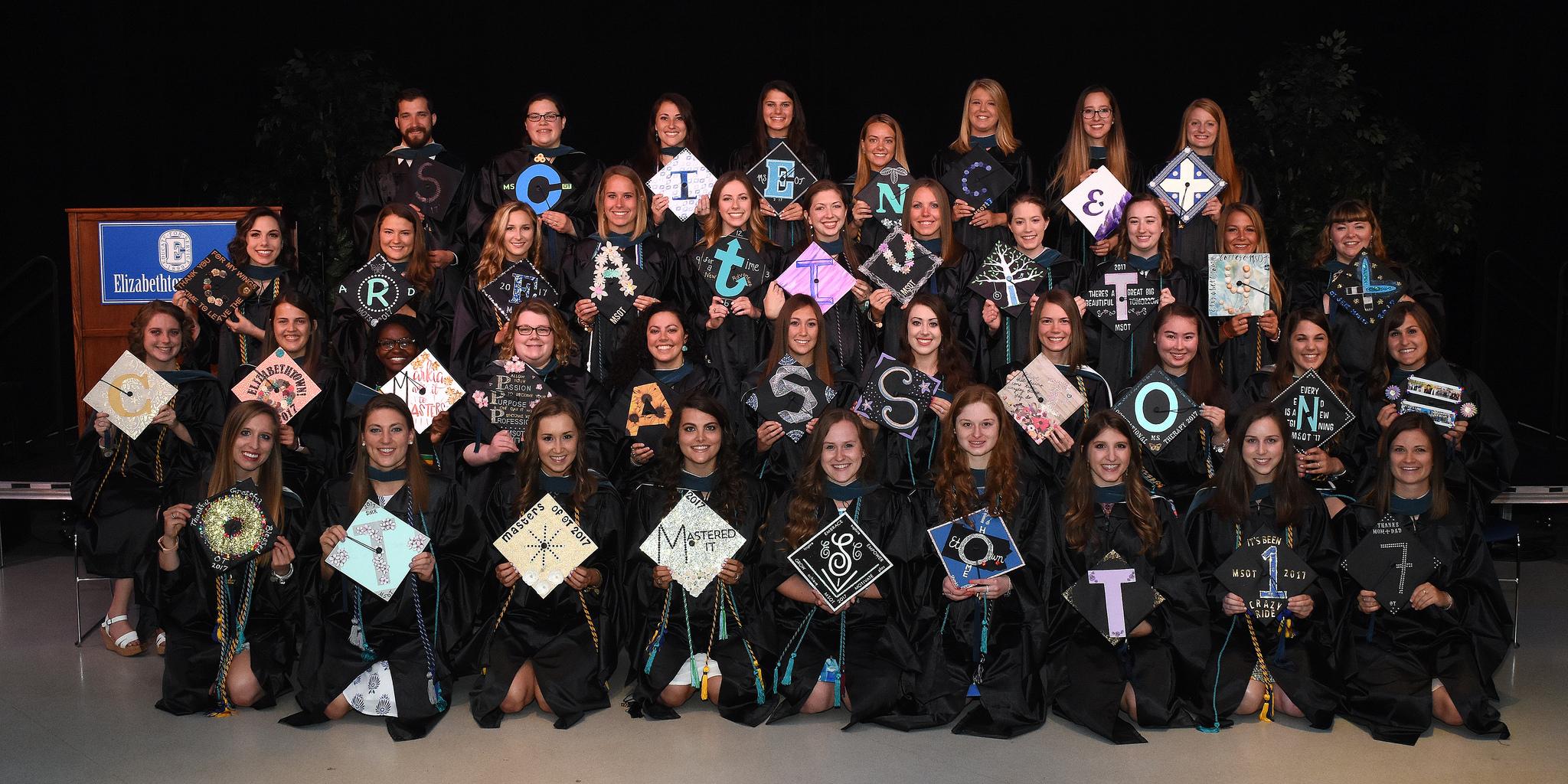 39 graduates in academic regalia holding caps